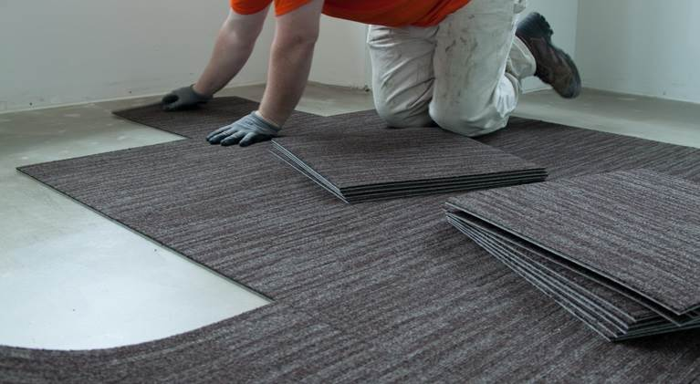 Worker on his knees installing carpet tiles.